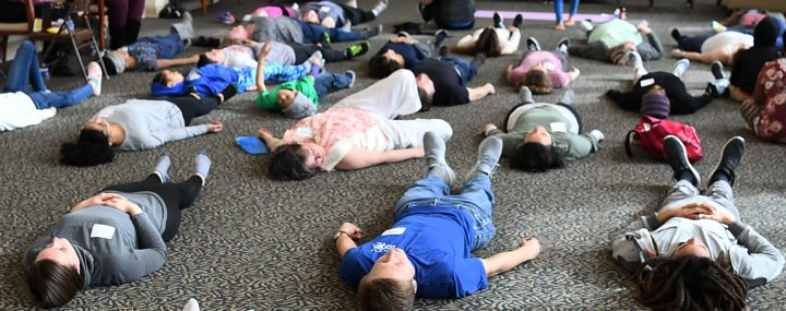 adults and children relaxing during yoga